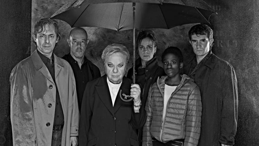 Imagen de los actores de la función de teatro Los otros Gondra donde se les puede ver a todos juntos bajo un paraguas