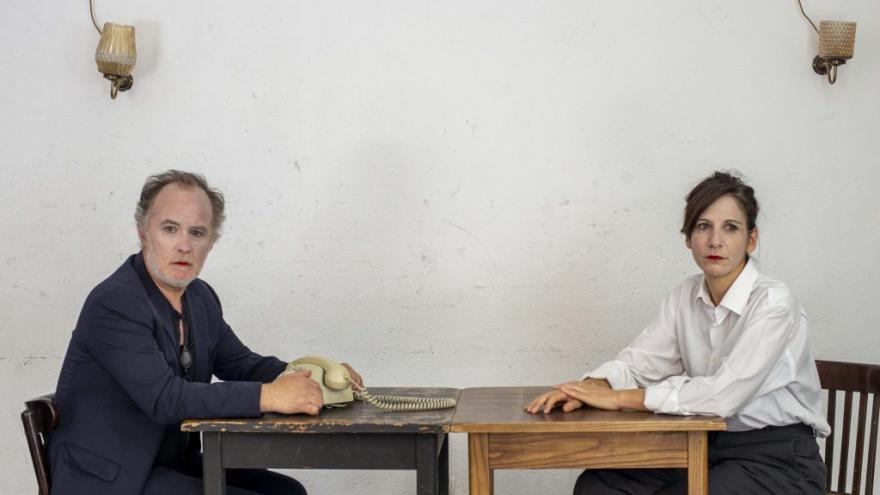 imagen en la que se ve a los dos actores del reparto hablando sentados a una mesa