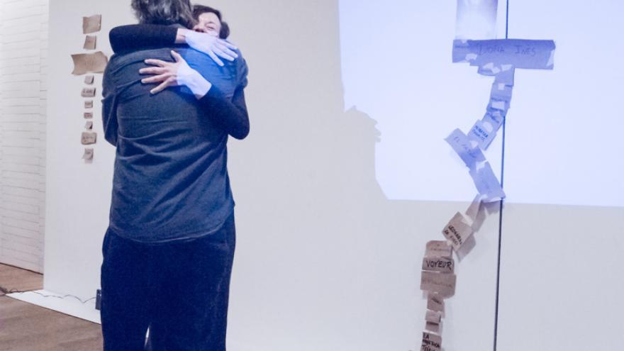 Dos personas abrazándose frente a una instalación artística