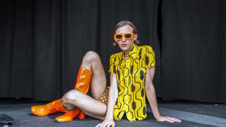 Modelo posando sentando en el suelo vestido como de los años 70