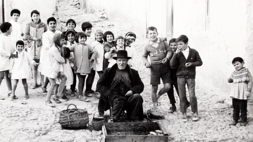 Hombre con sombrero sentado en la calle rodeado de niños