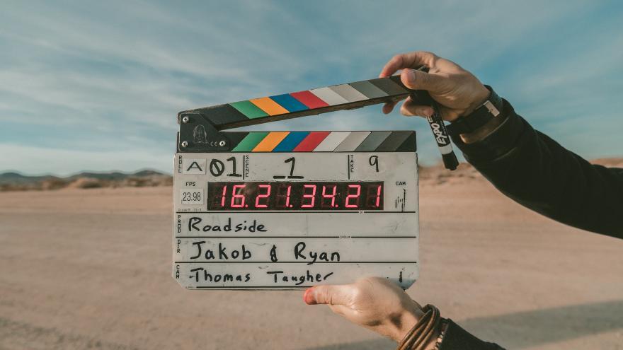 Claqueta de cine de colores, manejada por dos manos en una escena exterior