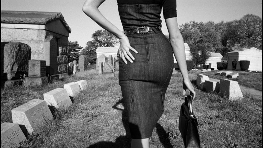 Foto en blanco y negro de una mujer de espaldas andando en un cementerio