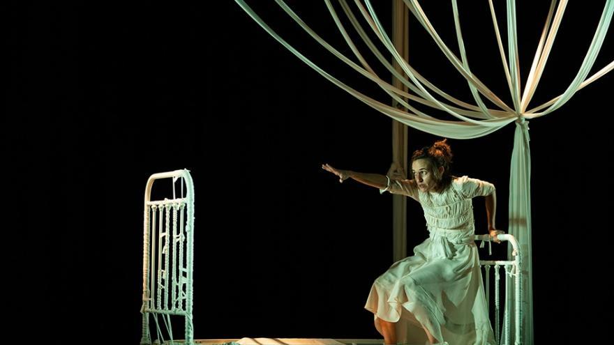 imagen de una actriz frente a la estructura de una cama actuando