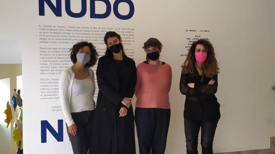 Artistas y comisarias posando delante del cartel que anuncia la exposición Nudo Nido