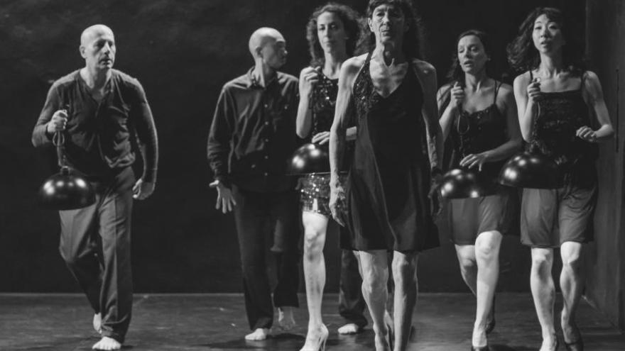 imagen en la que se ve a los bailarines andando por el escenario con unas lámparas en la mano