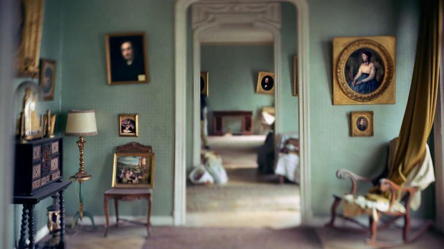 Interior de una casa antigua con mobiliario envejecido y paredes en color verde llenas de lienzos enmarcados con cuadros del siglo XIX