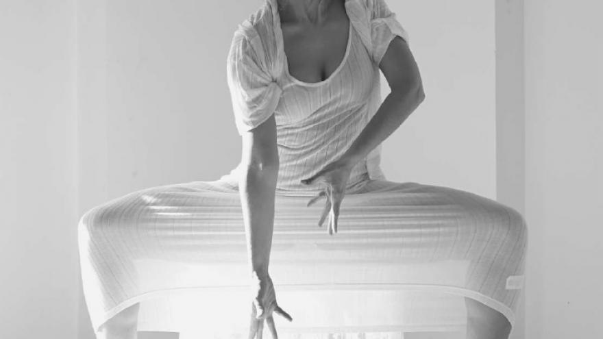 imagen en la que se ve a Mónica Iglesias vestida de blanco sentada en una postura bailando