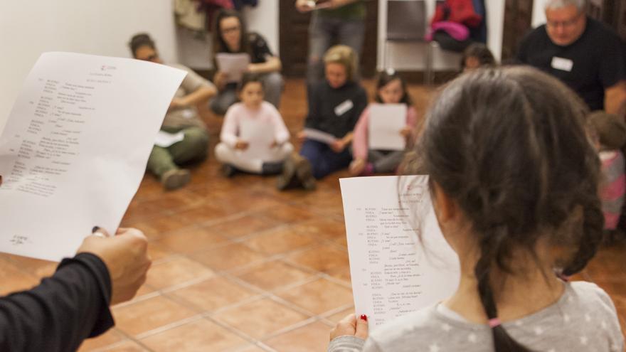 Niños y niñas sentados en el Museo Lope de Vega mientras otros dos leen unos textos