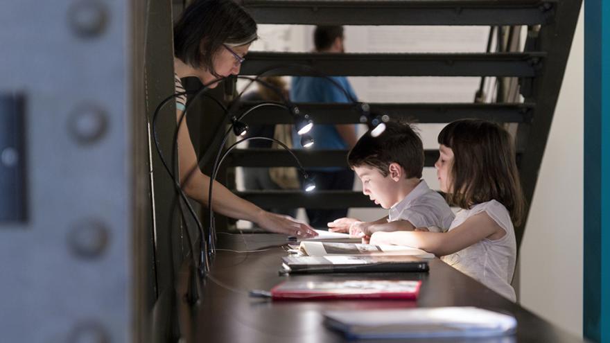 Dos niños mirando un libro en una vitrina de una sala de exposiciones