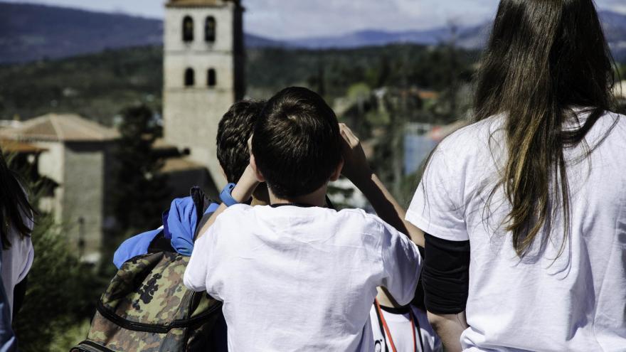 Niños y niñas con prismáticos viendo el pueblo de Manzanares El Real