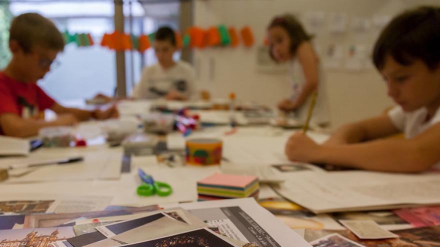 Grupo de niños en torno a una mesa recortando y pegando periódicos