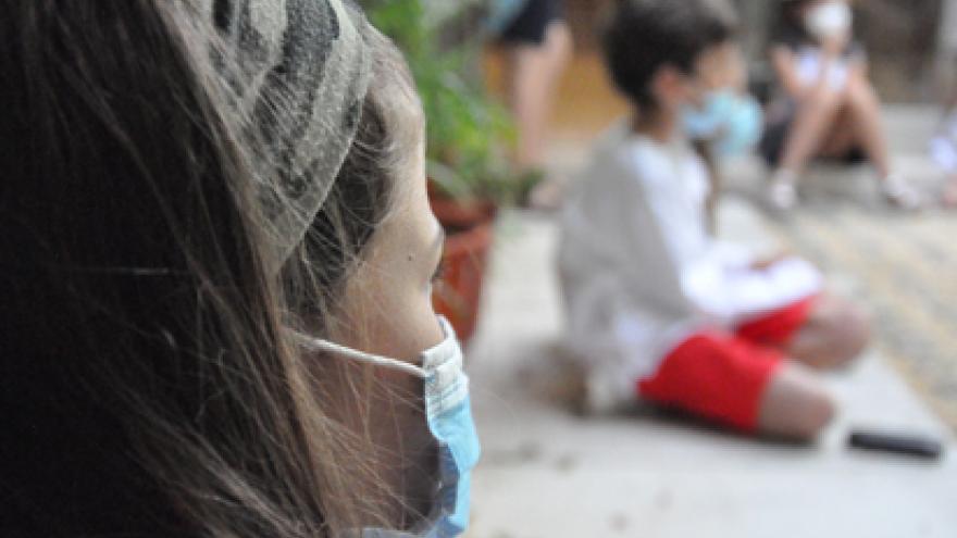 Niños y niñas con mascarilla en el patio del museo