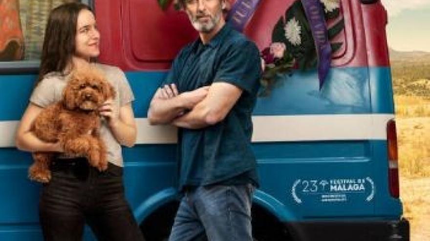 imagen de dos de sus protagonistas delante de una furgoneta de colores