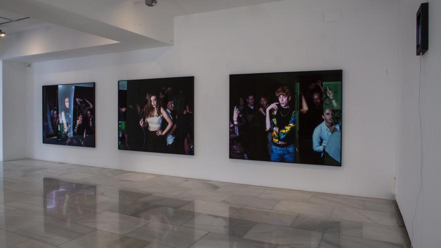 Tres fotografías de gran formato colgadas en una pared blanca