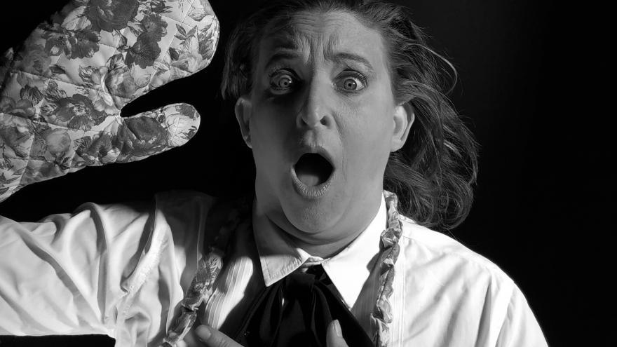 imagen en la que se ve a la actriz en escena con un guante de cocina y un delantal