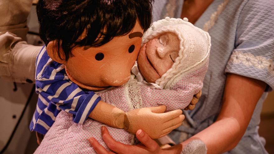 imagen en la que se ve a una marioneta de un niño cogiendo en brazos a un bebe