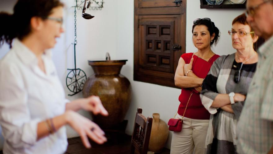 Grupo de personas escuchando a una mediadora cultural durante una visita a la Casa Museo Lope de Vega