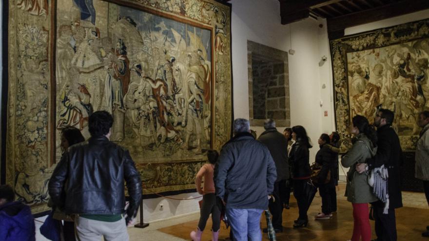 Grupo de personas adultas en una visita guiada en el castillo frente a un tapiz Barroco