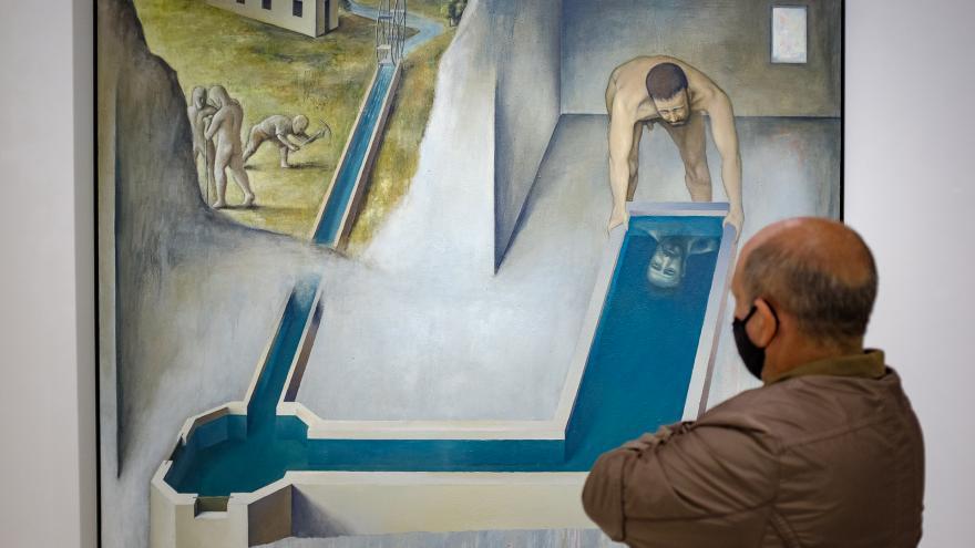 Hombre adulto con mascarilla observando un cuadro donde aparecen unos bañitas