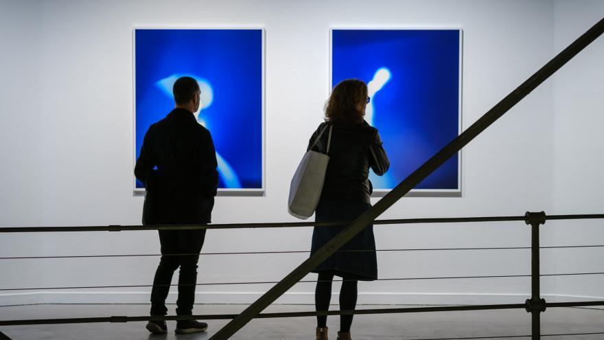 Dos visitantes frente a dos fotografías de Tanit Plana en la Sala Canal