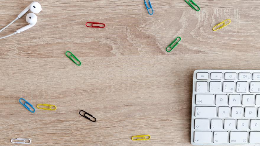Teclado de ordenador y clips de colores sobre mesa de madera