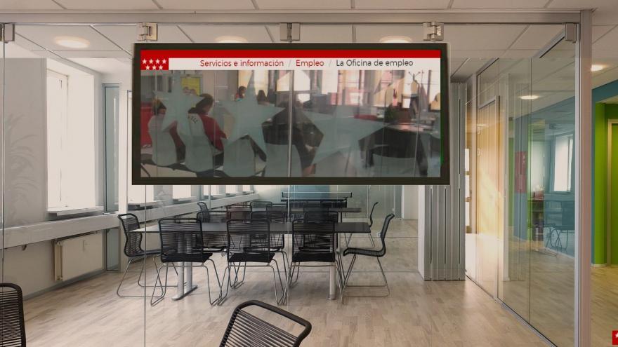 Oficina sin gente con un televisor proyectando la web de la Oficina Virtual de Empleo de la Comunidad de Madrid