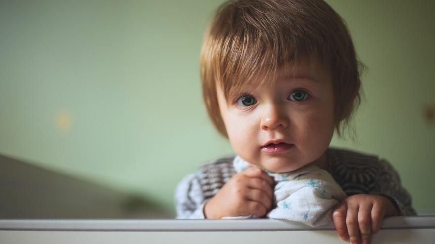 Niño de frente agarrado a muselina asomado a una barandilla