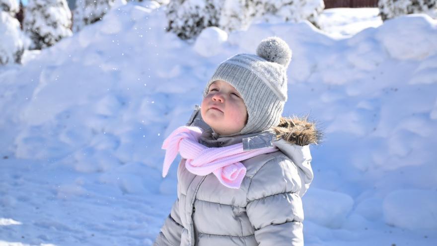 Niño con gorro de pie en la nieve