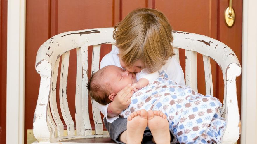 Niño y bebé sentados en un banco