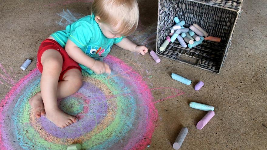 Niño pintando con tizas.