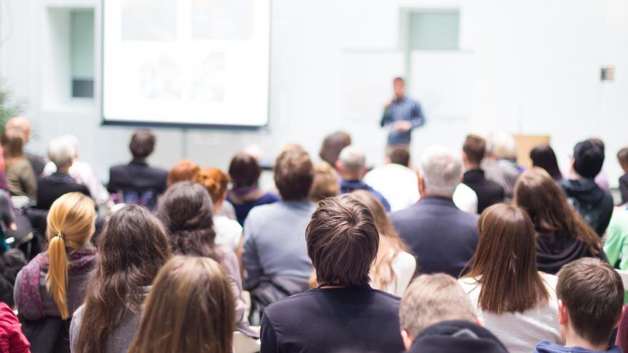 Un grupo de personas sentadas en un aula, escuchando a un conferenciante que está al fondo, delante de una pared y de una pizarra
