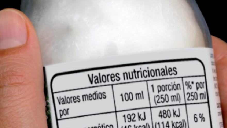Manos con un yoghurt etiquetado con la información nutricional