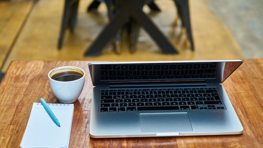 Ordenador, libreta y taza de café