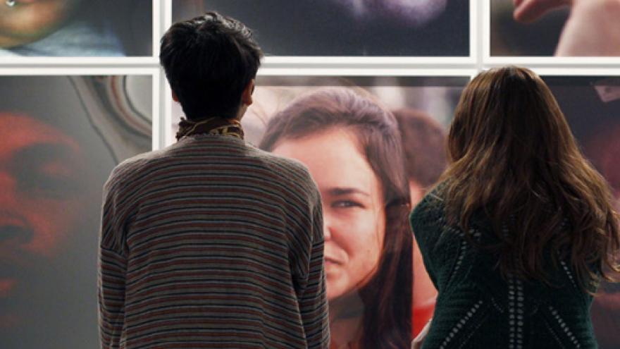 Dos mujeres sentadas de espaldas al espectador y mirando una pared llena de fotografías con retratos en color de personas anónimas