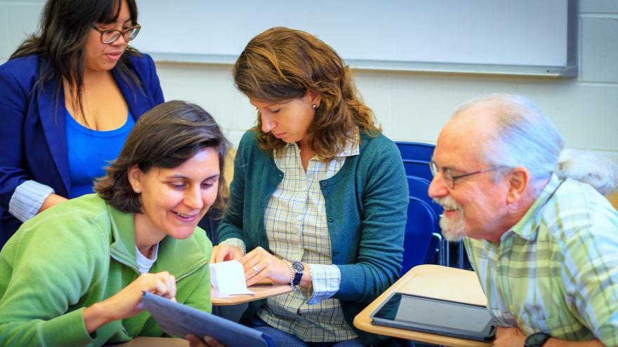 Adultos en un aula estudiando.