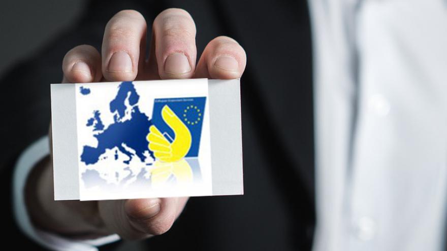Mano ofreciendo una oportunidad de trabajo contenida en una tarjeta que muestra el Mapa de la Unión Europea