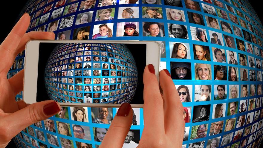 Teléfono movil haciendo una foto a un panel de videoconferencia donde aparecen muchas personas