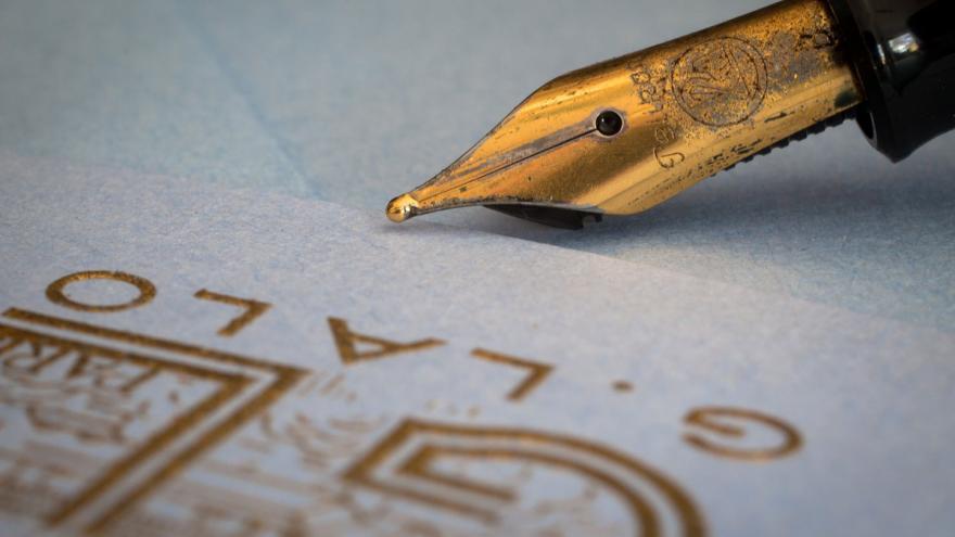 Punta dorada de una estilográfica y hoja de papel