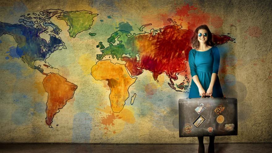 Mapa del mundo pintado en una pared y una mujer delante de él sostiene una maleta con ambas manos