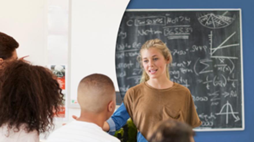 Una mujer impartiendo clase a unos alumnos, con pizarra al fondo
