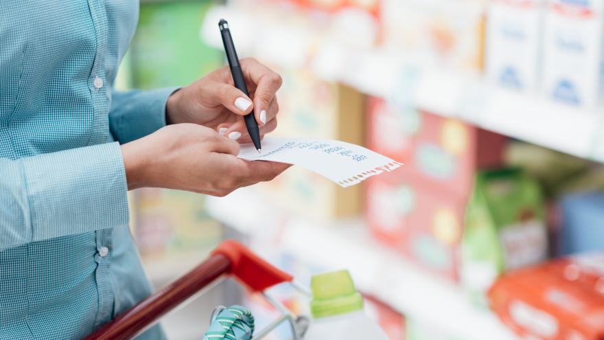 Mujer en supermercado con lista de la compra