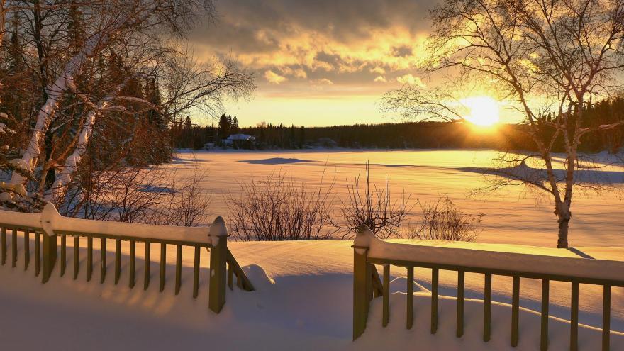 Paisaje nevado al atardecer, con una valla en primer, un campo lleno de nieve y árboles