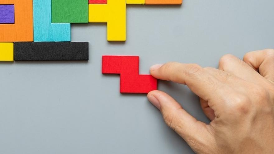 Foto de una mano haciendo un tetris con piezas de colores