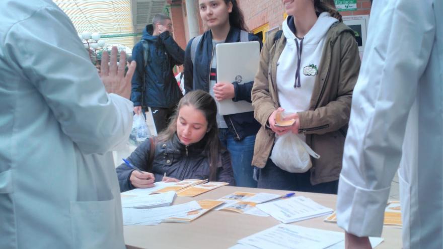 Alumnos reciben información en una mesa con folletos atendida por una enfermera en el hall de una facultad