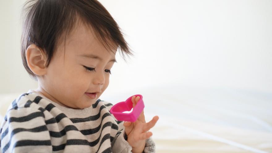 Niño pequeño jugando con corazón de plástico