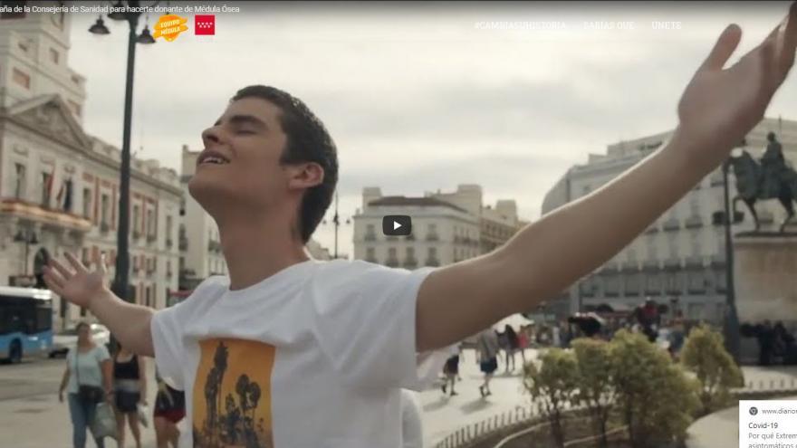 Imagen de vídeo con un joven en primer plano abriendo los brazos y mirando al cielo en la Puerta del Sol
