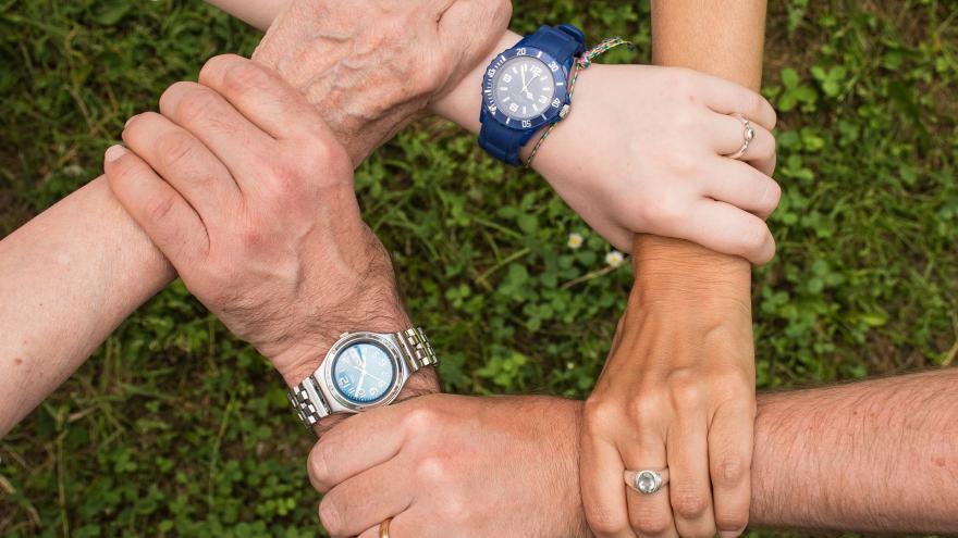 Manos de personas mayores y jóvenes entrelazadas en señal de trabajo en equipo