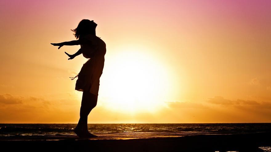 Silueta de mujer con el sol de fondo, con gesto de fellicidad