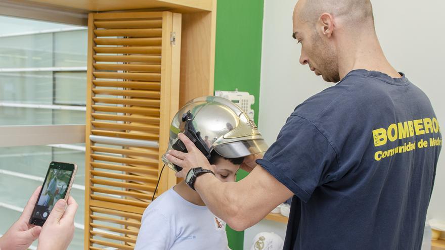bombero pone su casco a un niño